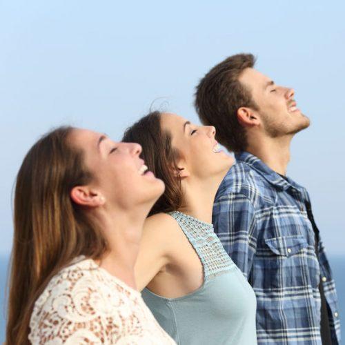 Profile of three happy friends breathing deep fresh air on the beach