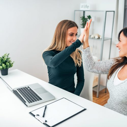 Two young business women giving high-five in modern office. Celebrating success.